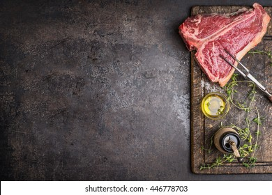 Raw T-bone Steak for grill or BBQ with meat fork and flavoring on aged cutting board and dark rustic metal background, top view, border