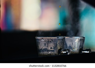 Raw tea drops falling inside the glass cups isolated unique photograph