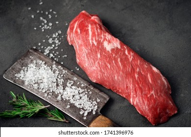 Raw tenderloin of beef or skirt steak with a hatchet for meat, salt and rosemary on a dark stone background, close up