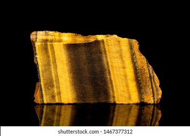 Raw tiger eye mineral stone in front of black background, mineralogy and esotericism