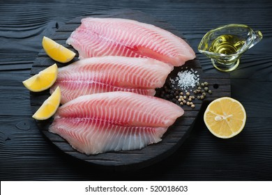 Raw tilapia fillet with seasonings on a wooden chopping board, studio shot