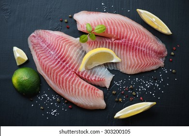 Raw tilapia fillets with seasonings over black wooden background