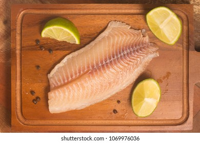 Raw Tilapia. Fish Fillet over a wooden table