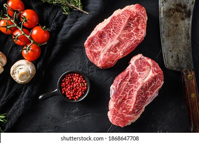 Raw top blade flat Iron beef cut organic meat ner butcher meat clever knife for bbw or gtrill over black stone background top view