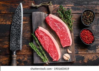 Raw top sirloin beef meat steak on a cutting wooden board. Dark wooden background. Top view.