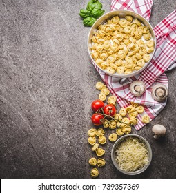 Raw tortellini pasta in bowl with ingredients, ready for cooking on rustic background , top view . Italian cuisine food concept