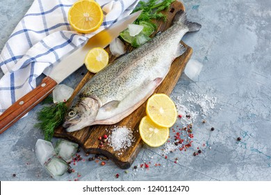 Raw trout, lemon slices, salt and ice cubes on wooden chopping board, selective focus.