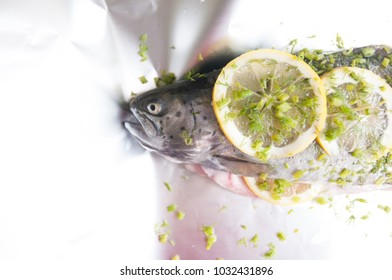 Raw trout ready for cooking lying on aluminum foil before goint to be baked