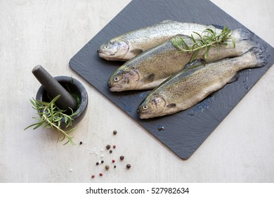 Raw trouts on gray board ready for cooking - Shutterstock ID 527982634
