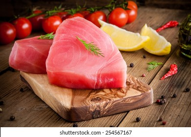 Raw tuna fillet with dill, lemon and cherry tomatoes in olive cutting board