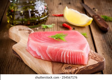 Raw tuna fillet with dill, lemon and olive oil on rustic background