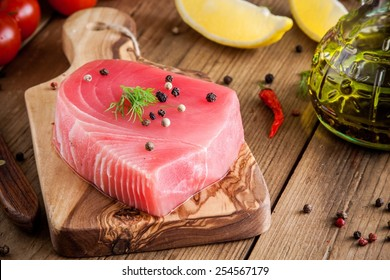Raw tuna fillet with dill, lemon and peppers in olive cutting board