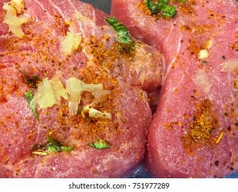 Raw tuna steaks with garlic and parsley, closeup