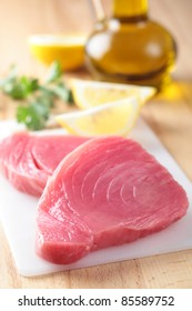 Raw tuna steaks with lemon  and cooking oil on a cutting board