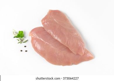 raw turkey breasts with spice and herbs on white background
