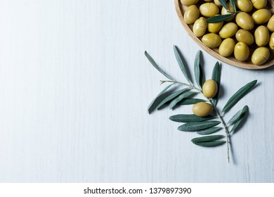 raw turkish green olive seeds, olive tree branch with leaves on white table. olives background, olivae oleum