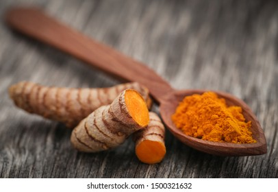 Raw turmeric with powder in wooden spoon