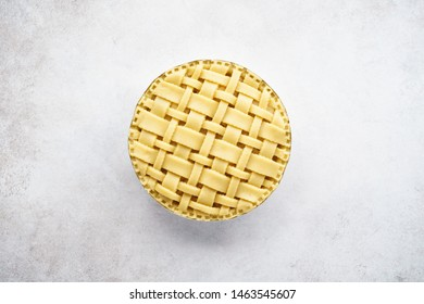Raw unbaked apple pie with lattice top on light gray concrete background. Top view. Space for text.