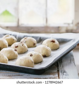 Raw unbaked buns. Ready to bake homemade Easter traditional hot cross buns on oven tray with baking paper over white wooden table with window at background. Natural day light. Square image