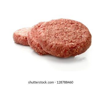 Raw uncooked beef burgers stacked against a white background with soft shadows. Copy space.