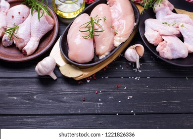 Raw uncooked chicken breast, wings,  legs or drumsticks  with ingredients for cooking on  black wooden background. Selective focus. Place for text.