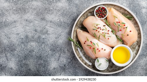 Raw uncooked chicken breasts with spices and herbs on gray concrete table, chicken meat with ingredients for cooking. Top view