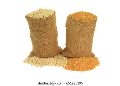 Raw (uncooked) Israeli and Tricoloured (Tri-colored, Tricolor, Tri color) Couscous (cous-cous) colored by tomato and spinach powders in burlap bags and spilled out on piles white background-isolated