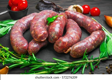 Raw uncooked meat sausages on a black cutting board. Spices for raw meat sausages onions, garlic, thyme, rosemary, sage leaves, cilantro, peppers, cherry tomatoes. Dark rustic wooden background.