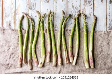 Raw uncooked organic green asparagus in row on linen cloth over white wooden plank background. Top view, space.