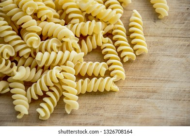 Raw uncooked pasta fusilli, background texture. Fusilli are a variety of pasta that are formed into corkscrew or helical shapes.