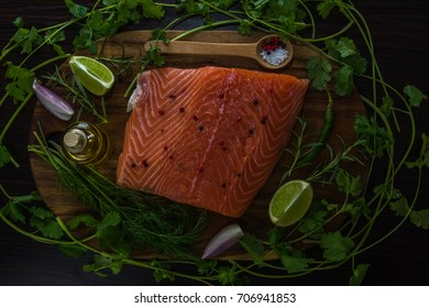 Raw uncooked salmon fillet with vegetables, herbs and spices  on a wooden background, top view.