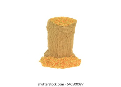 Raw, uncooked Tri-colored (Tricolor), (Tri color) cous-cous (couscous) colured with tomato and spinach powder in burlap bag (sack) and spilled on pile, over white background - isolated