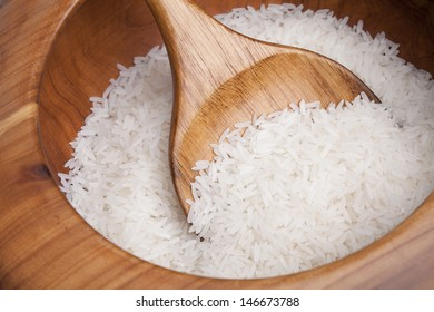 Raw, uncooked white rice in a wooden bowl with spatula