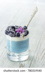 Raw Vegan Blue Spirulina Chia Pudding with Whipped Coconut Cream and Frozen Blueberries and Blackberries