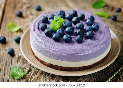 Raw vegan Blueberry Cashews cake on a wood background. toning. selective focus