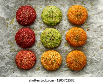Raw vegan burgers made of beetroot, green peas, carrots, groats and herbs on white parchment prepared for baking, top view