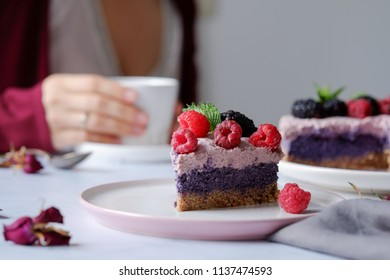 Raw vegan cake with raspberries and bluberries on white table