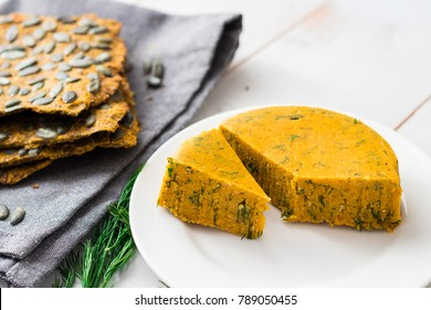 Raw vegan cheese with cashew, almond, carrot, pumpkin and herbs. With healthy flax and pumpkin seeds bread. Healthy food concept.