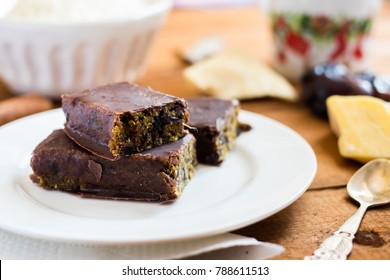 Raw vegan chocolate energy bars. Dates, nuts, cocoa, honey. Served on white plate.