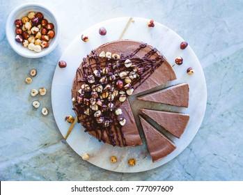 Raw vegan chocolate vanilla cheesecake  with hazelnuts on marble table, background.