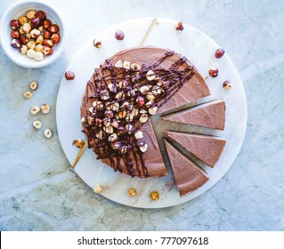 Raw vegan chocolate vanilla cheesecake  with hazelnuts on marble table, background. Top view. Toning.