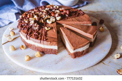 Raw vegan chocolate vanilla cheesecake  with hazelnuts on marble table, background. Top view. Toning. Selective focus.