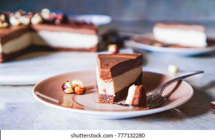 Raw vegan chocolate vanilla cheesecake  with hazelnuts on marble table, background. Top view. Toning. Selective focus. Close up.
