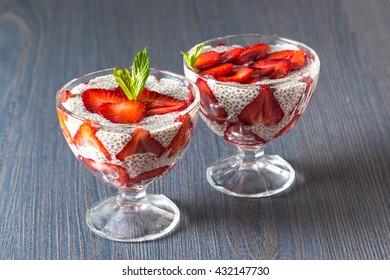 Raw vegan dessert: Chia seeds pudding with strawberries on a dark background