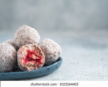 Raw vegan lamington bliss balls with raspberries chia jam on gray background. No baked healthy vegan sweet dessert idea and recipe. Top view or flat-lay.