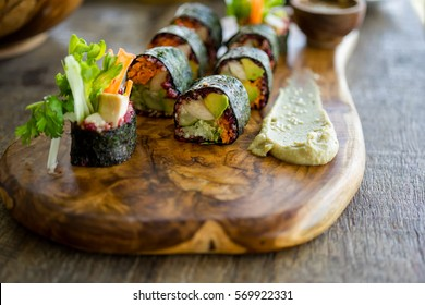 Raw vegan nori hand rolls with pink horseradish sauce, salad and vegetables. On a slate plate against a wooden background. Vegetarian, gluten-free food.