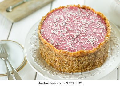 Raw Vegan Paleo Diet Berry Cheesecake Gluten-Free with Dates and Cashews on a Light White Wooden Background, Horizontal