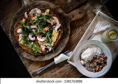 Raw vegan pizza and smoothie bowl on wooden table at restaurant. Food photography concept, top view