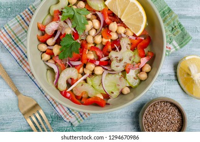 Raw vegetable salad with chickpeas and flax seeds on wooden background. Selective focus.