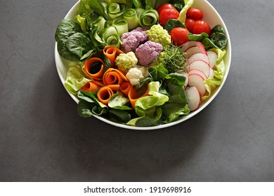 Raw vegetable salad with colorful cauliflower, lettuce, radish and tomato. Selective focus